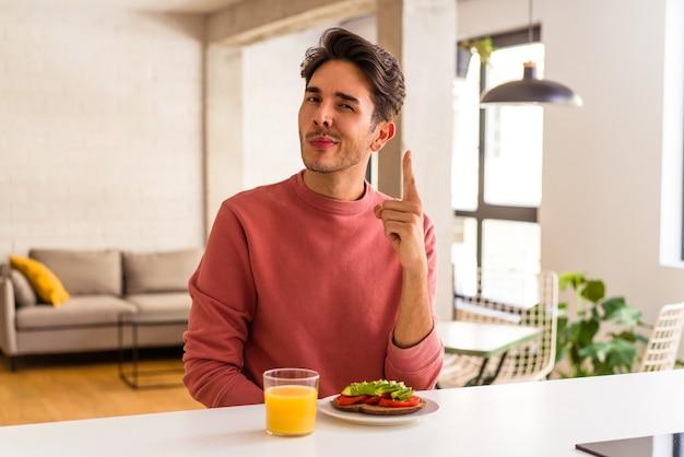 Jeune homme de race mixte prenant son petit déjeuner dans sa cuisine montrant le numéro un avec le doigt.