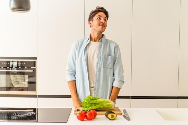 Jeune homme de race mixte préparant une salade pour le déjeuner rêvant d'atteindre des objectifs et des objectifs