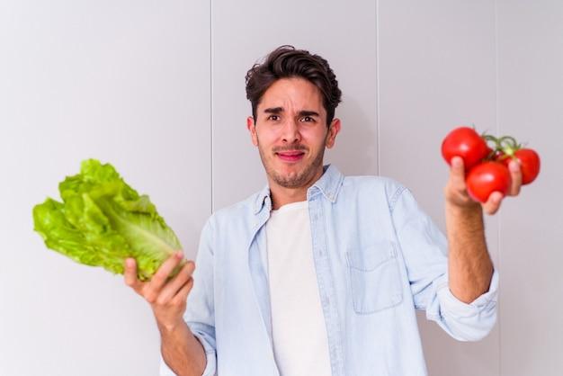 Jeune homme de race mixte préparant une salade pour le déjeuner