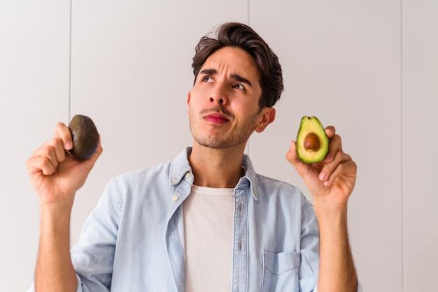 Jeune Homme De Race Mixte Tenant Des Avocats Dans Sa Cuisine Photo Premium