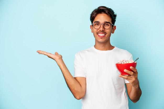 Jeune homme de race mixte tenant des céréales isolées sur fond bleu montrant un espace de copie sur une paume et tenant une autre main sur la taille.