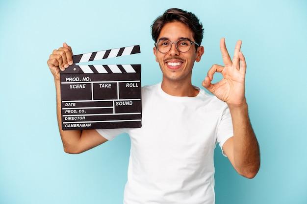 Jeune homme de race mixte tenant un clap isolé sur fond bleu joyeux et confiant montrant un geste ok.