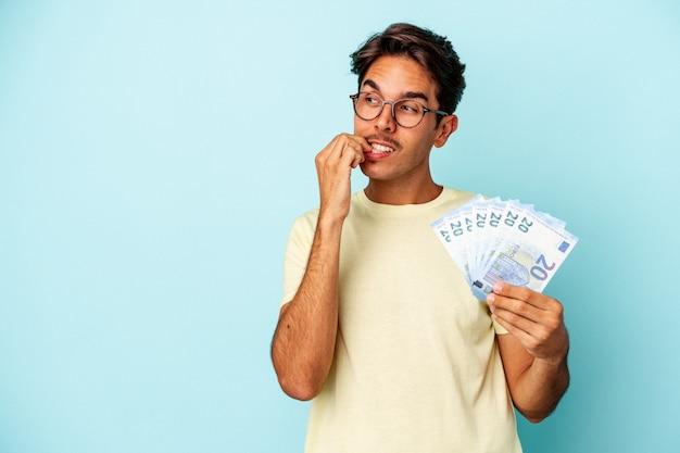 Jeune homme de race mixte tenant des factures isolées sur fond bleu détendu en pensant à quelque chose en regardant un espace de copie.