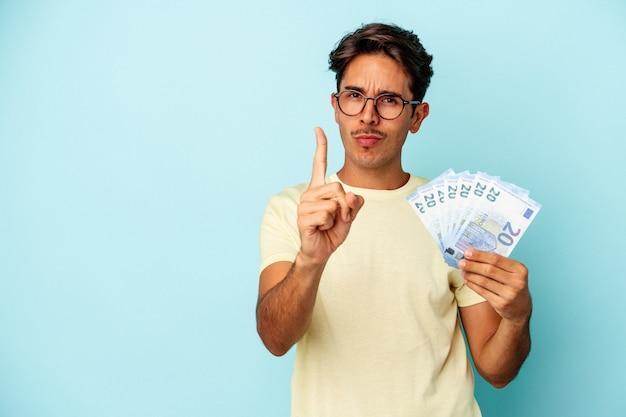 Jeune homme de race mixte tenant des factures isolées sur fond bleu montrant le numéro un avec le doigt.