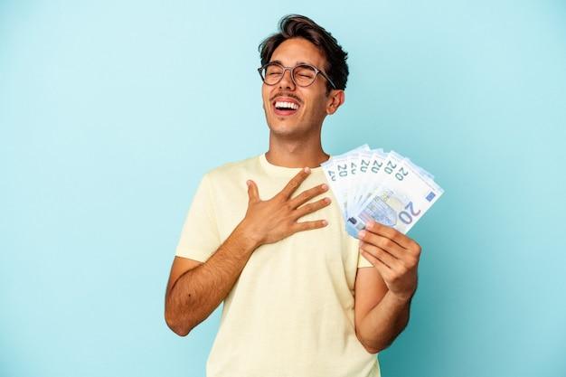 Jeune homme de race mixte tenant des factures isolées sur fond bleu rit fort en gardant la main sur la poitrine.