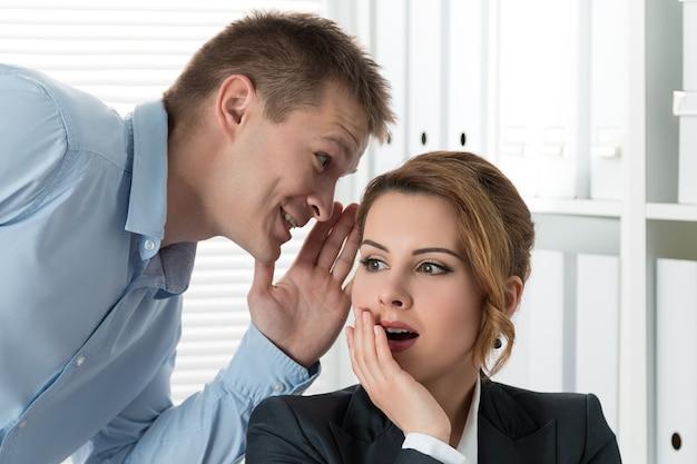 Jeune homme racontant des potins à sa collègue au bureau. intrigues et concept de perte de temps