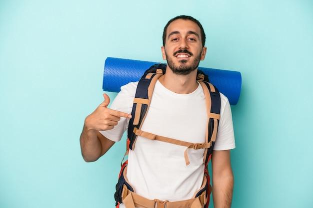 Jeune homme de randonnée caucasien isolé sur fond bleu personne pointant à la main vers un espace de copie de chemise, fier et confiant