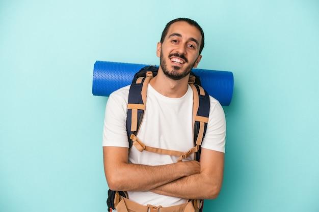 Jeune homme de randonnée caucasien isolé sur fond bleu en riant et en s'amusant.