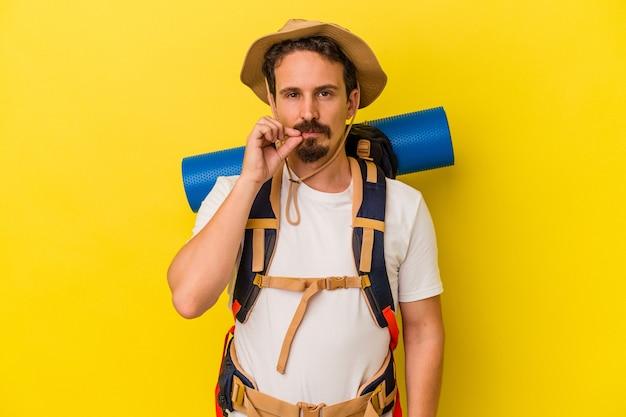 Jeune homme de randonnée caucasien isolé sur fond jaune avec les doigts sur les lèvres gardant un secret.