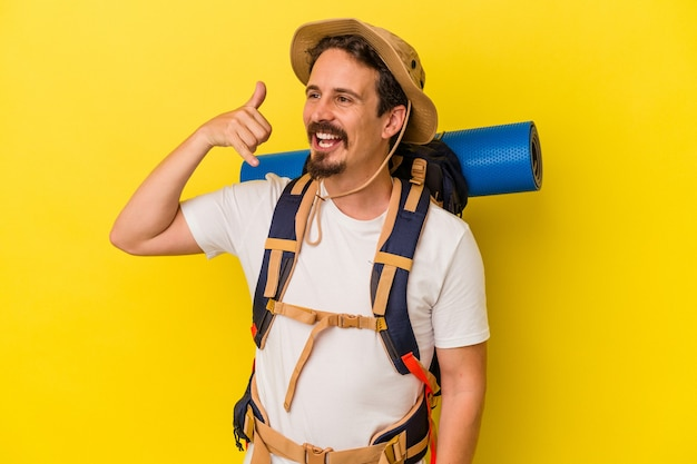 Jeune homme de randonnée caucasien isolé sur fond jaune montrant un geste d'appel de téléphone portable avec les doigts.