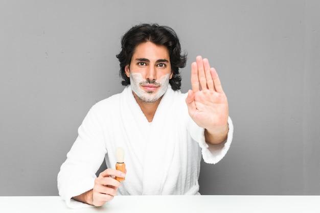 Jeune homme rasant sa barbe debout avec la main tendue montrant le panneau d'arrêt