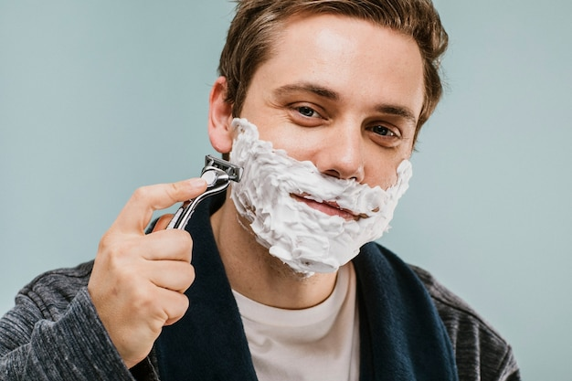 Jeune homme rasant sa barbe