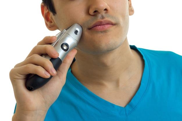 Jeune homme rase ses machines à raser la barbe à l'aide de gros plan isolé sur mur blanc