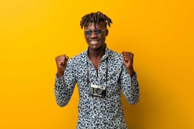 Jeune homme rasta noir portant un look de vacances levant le poing, se sentant heureux et réussi. concept de victoire.