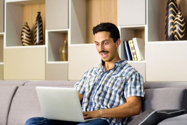 Jeune homme réagissant avec étonnement à un ordinateur portable regardant les yeux écarquillés avec sa bouche ouverte alors qu'il se détend à la maison sur un canapé confortable