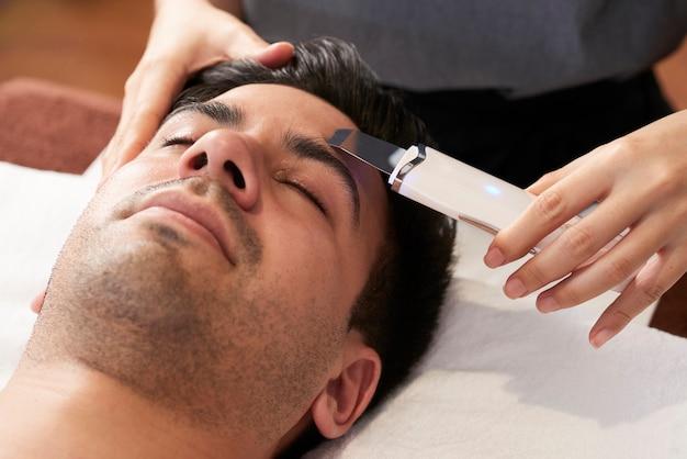 Jeune homme recevant un traitement de nettoyage de la peau du visage avec une spatule à ultrasons dans un salon de beauté