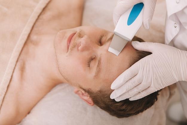 Jeune homme recevant un traitement de soin du visage par un cosmétologue