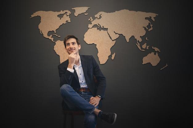 Jeune homme à la recherche de la carte du monde avec les mains croisées