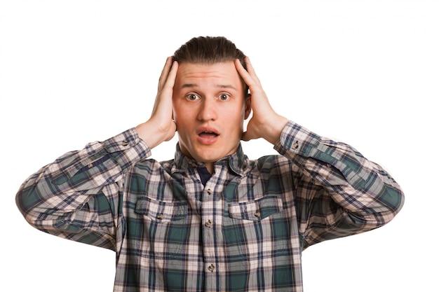 Jeune homme à la recherche de choqué, posant isolé sur blanc. homme séduisant à la recherche accablé avec ses mains à sa tête. surprise, étonnement, concept d'émotions