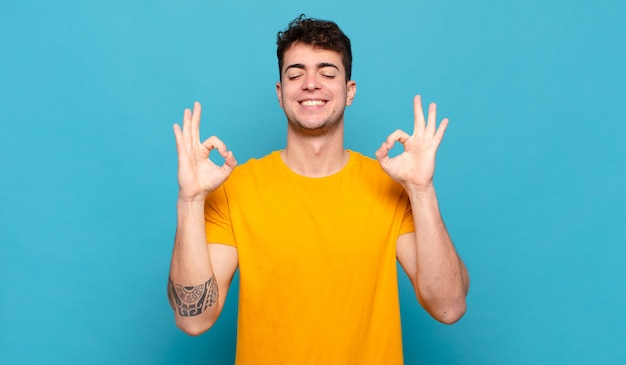 Jeune homme à la recherche de concentré et de méditation, se sentir satisfait et détendu, penser ou faire un choix