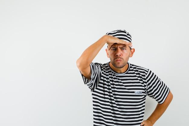 Jeune homme à la recherche de loin avec la main sur la tête en chapeau t-shirt rayé