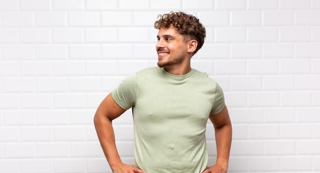 Jeune homme à la recherche de plaisir, de bonne humeur et confiant, souriant fièrement et à la recherche de côté avec les deux mains sur les hanches