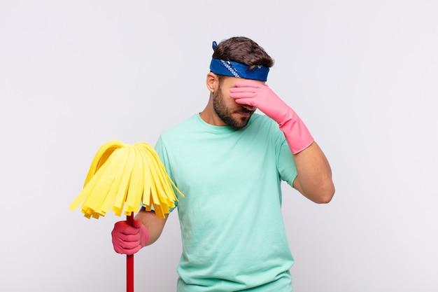Jeune homme à la recherche de stressé, honteux ou bouleversé, avec un mal de tête, couvrant le visage avec la main