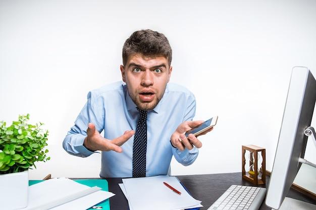 Le jeune homme reçoit un message horrible et choquant. je ne peux pas en croire ses yeux, perd son équilibre sous le choc, s'énerve et se met en colère. concept des problèmes de l'employé de bureau, des affaires, des problèmes d'information.