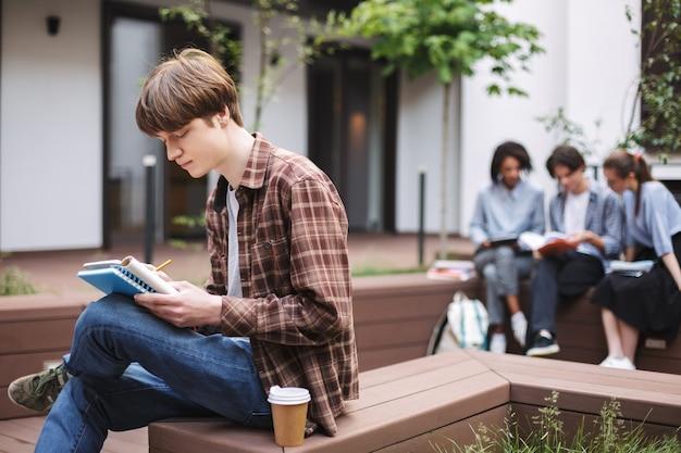 Jeune homme réfléchi assis sur un banc avec du café et de l'écriture dans un ordinateur portable tout en passant du temps dans la cour de l'université avec des étudiants en arrière-plan