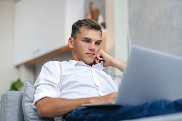 Jeune homme réfléchi naviguant sur internet en position couchée sur le canapé