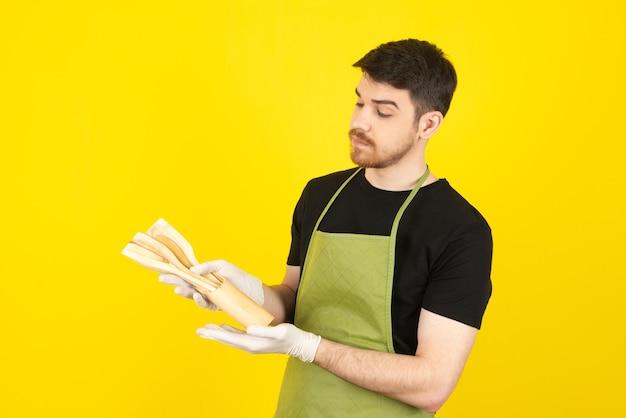 Jeune homme réfléchi regardant des cuillères sur un jaune.