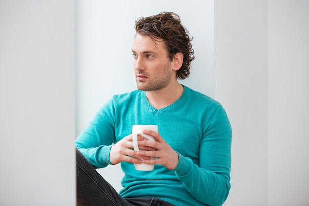 Jeune homme réfléchi s'asseyant sur le rebord de la fenêtre et buvant du café