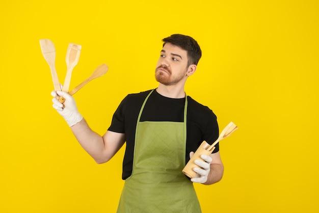 Jeune homme réfléchi tenant des cuillères en bois sur jaune.