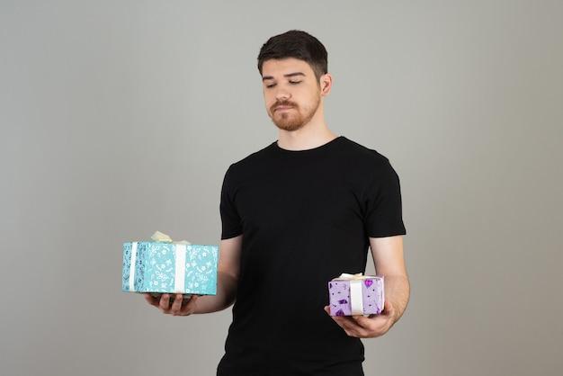 Un jeune homme réfléchi tenant deux cadeaux et les regardant.