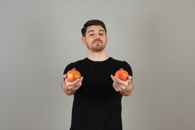 Jeune homme réfléchi tenant des fruits frais et le regardant.