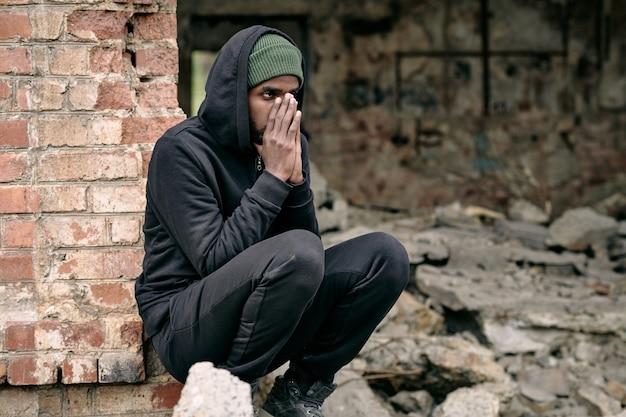 Jeune homme réfugié noir affolé en tenue noire accroupi devant un bâtiment en ruine et couvrant le visage avec...