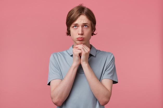 Jeune homme avec un regard de mendicité priant regarde vers le haut, les bras et les doigts serre le poing en se tenant debout sur fond rose. espérant, souhaitant, priant, attendant un miracle