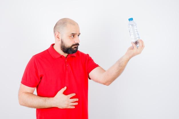 Jeune homme regardant une bouteille pleine d'eau en chemise rouge , vue de face.