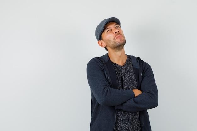 Jeune homme regardant avec les bras croisés en t-shirt, veste, casquette et regardant pensif, vue de face.