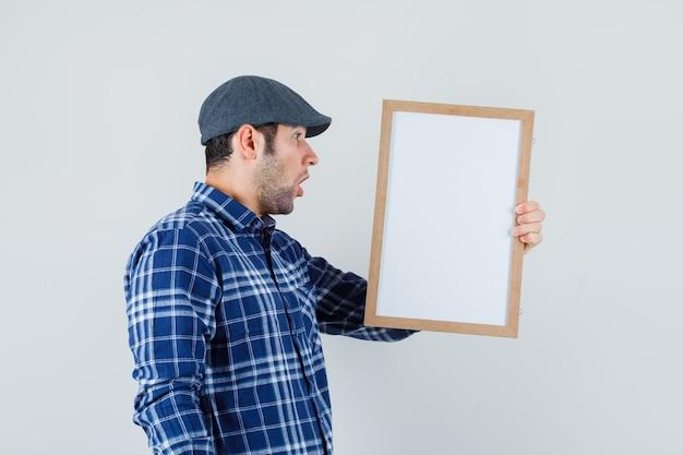 Jeune homme regardant un cadre vide en chemise, casquette et à la vue de face, étonné.