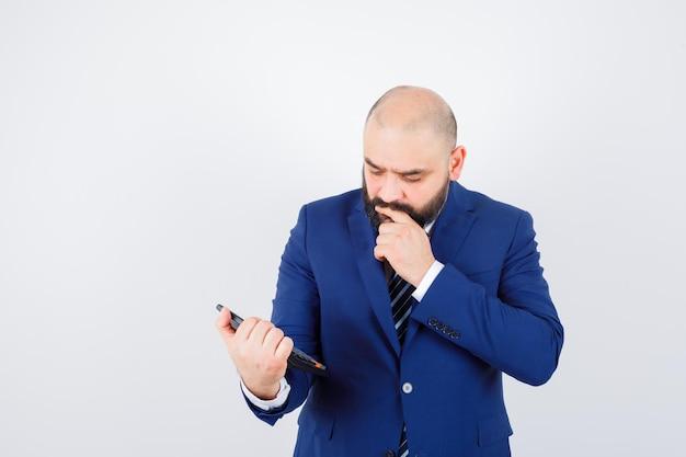 Jeune homme regardant la calculatrice en chemise blanche, veste et pensif. vue de face.