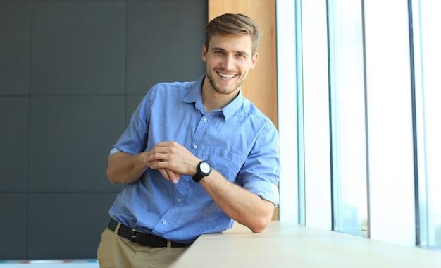 Jeune homme regardant la caméra dans son bureau.