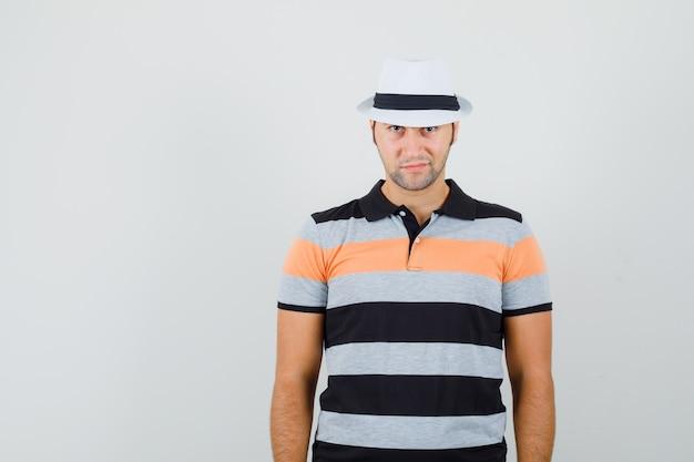 Jeune homme regardant la caméra en t-shirt, chapeau et à la recherche de calme