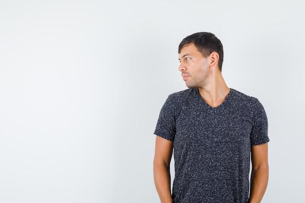 Jeune homme regardant de côté en t-shirt noir vue de face. espace pour le texte