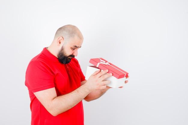 Jeune homme regardant dans une boîte-cadeau en t-shirt rouge et se demandait. vue de face.