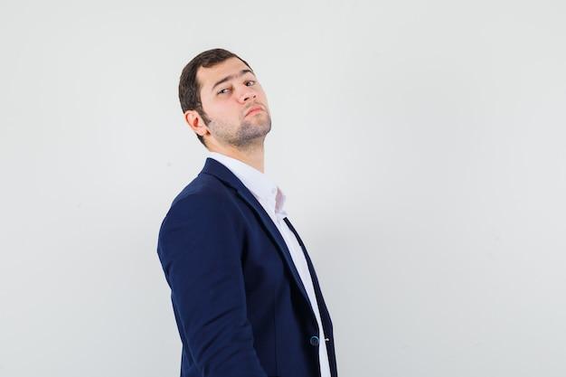 Jeune homme regardant devant en chemise et veste et à la confiance.