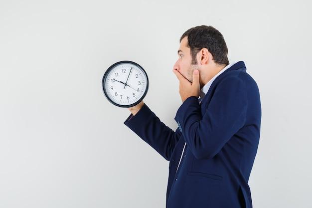 Jeune homme regardant horloge murale en chemise et veste et à la recherche d'anxiété. .