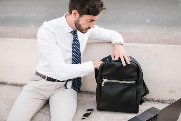 Jeune homme regardant à l'intérieur du sac à dos noir