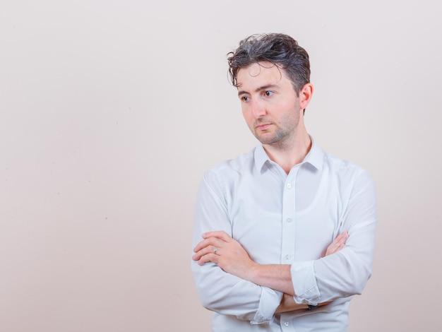 Jeune homme regardant loin avec les bras croisés en chemise blanche et à la réflexion