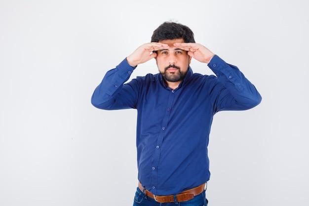 Jeune homme regardant avec les mains au-dessus de la tête en chemise bleue et regardant concentré, vue de face.